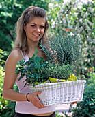 Junge Frau mit Körbchen voll frisch gekaufter Kräuter