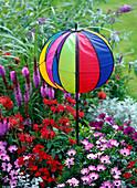 Ballförmiges buntes Windspiel in Beet
