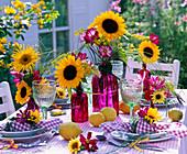 Tischdekoration mit Helianthus (Sonnenblumen), Cosmos (Schmuckkörbchen)