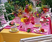 Tischdekoration mit Sträußen aus Zinnia (Zinnien), Solidago (Goldrute)