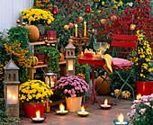Herbstliche Abendterrasse mit Laternen und Kerzen