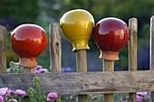 Gartenkugeln aus glasiertem Terrakotta auf Holzzaun