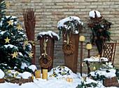 Weihnachtliches Arrangement auf verschneiter Terrasse