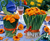 Calendula bouquets in vases with brassica
