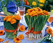 Sträuße aus Calendula (Ringelblumen) in Vasen, die mit Brassica (Wirsing)