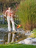 Junge Frau fischt Laub aus dem Teich