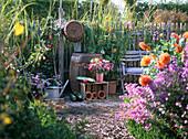 Sitzplatz im Bauerngarten neben Holzregenfaß