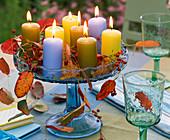 Hagebutten, Herbstlaub von Prunus (Kirsche), Kerzen auf Glas - Schale