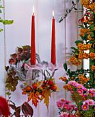 Kerzenhalter an der Wand dekoriert mit Herbstlaub von Acer (Ahorn), Hagebutten