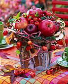 Gesteck aus Malus (Äpfeln, Zieräpfeln, getrockneten Apfelscheiben), Hedera