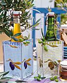 Flaschen mit Olivenöl in Tüten mit Oliven - Motiven, Zweige und Früchte von Olea