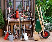 Gartengeräte auf der Terrasse : Schaufel, Gießkanne, Grabgabel, Rechen, Spaten