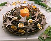 Windlicht mit oranger Kerze in Kranz aus Larix (Lärchenzweigen)