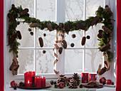 Fenster dekoriert mit gemischter Koniferengirlande mit Picea (Fichtenzapfen)