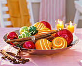 Citrus (Orangen, Limetten), Zimtstangen, Weihnachtsbaumkugeln in Schale