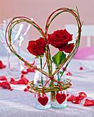 Rote Rosa (Rosen) in kleinen Flaschen, Herz aus Salix (Weide) und Peddigrohr