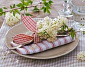 Syringa (Flieder), Dolde auf gefalteter rot - weißer Serviette, Besteck