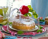 Ranunculus (Ranunkel) und Corylus (Haselnuss) auf Glasglocke über Kuchen