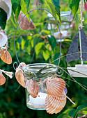 Windlicht mit Muscheln und Gras dekoriert in Baum hängend