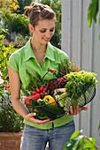 Frau mit frisch gekauftem Bio - Gemüse im Korb