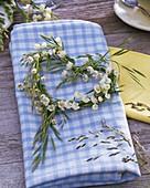 Kranz aus Convallaria (Maiglöckchen) und Gräsern in Herzform auf Serviette