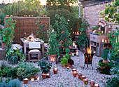 LOHAS - Serie: Abendliche Terrasse mit Kerzen und Feuerkorb, Lycopersicon (Tomate), Lathyrus odoratus (Duftwicken), Phaseolus coccineus (Feuerbohnen), Cucurbita (Zucchini), Topfturm und Kasten mit Kräutern