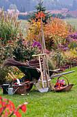 Arbeitsstil mit Gartengeräten vor Herbstbeet