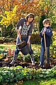 Mutter und Sohn pflanzen Ginkgo biloba (Ginkgobaum)