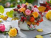Kleines Herbstgesteck in großer Tasse