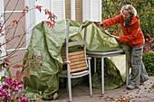 Gartenmöbel im Herbst mit grüner Plane einwintern