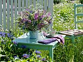 Sitzplatz in der Wiese am weißen Gartenzaun