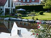 Blick vom Schwimmteich auf die Terrasse am Haus