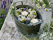 Kleiner Kranz aus Wiesenblumen im Wasser