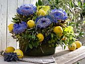 Gesteck aus Cynara scolymus (Artischocken), Citrus limon (Zitronen)