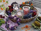 Windlichter in Korb mit getrockneten Kränzen, Beeren und Blüten