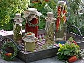 Flaschen mit Kräutern und Peperoni in Öl, Tomaten-Sugo und Kräuter-Sträuße