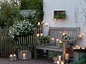 weiße Abendterrasse mit Windlichtern und Kerzen