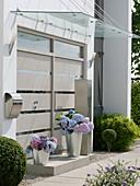 Moderner Hauseingang mit Glasvordach, Kübel mit Hortensien