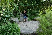 Kleiner Kiesplatz mit Granit - Blöcken , Junge sitzt auf Stein-Sessel