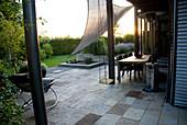 Blick von der beschatteten Terrasse auf das architektonische Wasserspiel