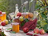 Drahtkorb mit Äpfeln, Apfelgelee und Apfelsaft