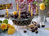 Drahtkorb mit Kastanien und Kerzen