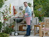 Outdoor - Küche auf dem Balkon : Mann grillt Aubergine, Töpfe mit Glockenchili