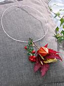 Floraler Schmuck mit Pysalis, Cotoneaster und Herbstlaub
