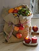 Korb mit Äpfeln (Malus) und Orangen (Citrus sinensis) im Jutesack