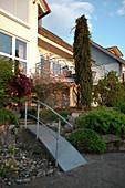 Kleine Brücke aus Stahl über Kiesbett als Zugang zum Haus in reich bepflanztem Garten