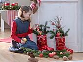 Mädchen neben roten Nikolausstiefeln, gefüllt mit Abies (Tanne), Äpfeln