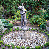 Boy Statue On PEDESTAL IN CENTRE of PEBBLE MOSAIC. Helen DILLON'S Garden DUBLIN.