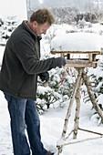 Mann hängt Meisenknödel ans Vogelfutterhaus