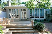STEPS AND DECKED COURTYARD GARDEN. QUERCUS STELLATA OVERHANGING. Gordon White'S Garden, Texas